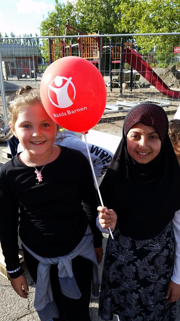 Barn håller upp röd ballong.