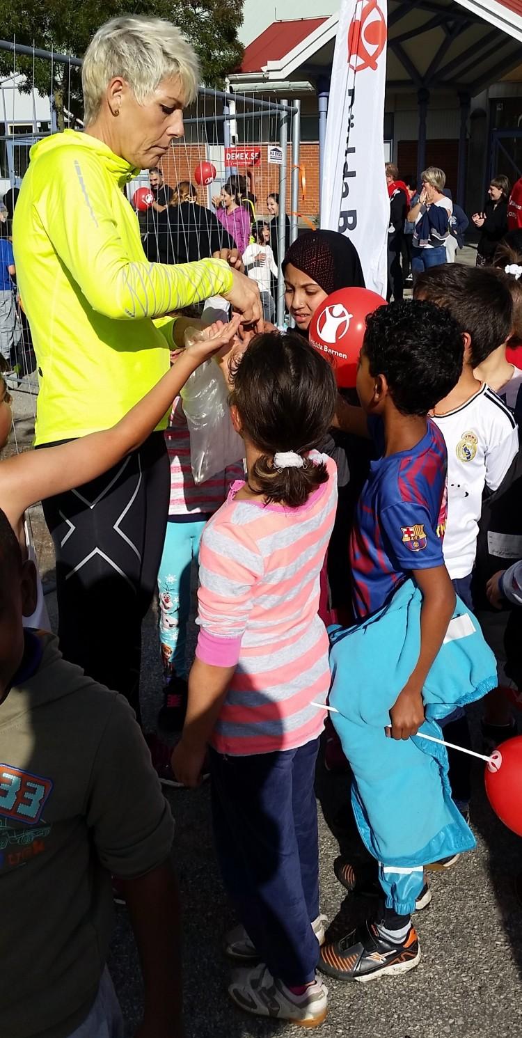 Kvinna delar ut till barnen.