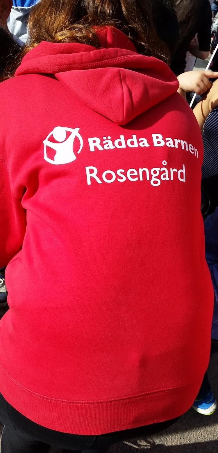 Kvinna med röd tröja där det står Rädda barnen Rosengård.