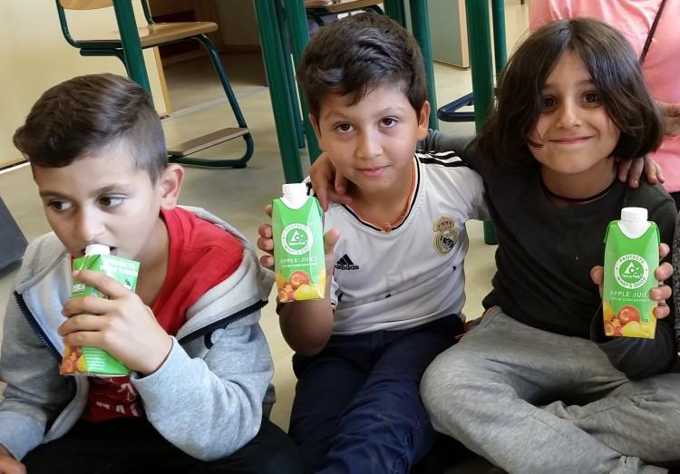 Tre barn dricker ur pappförpackning.