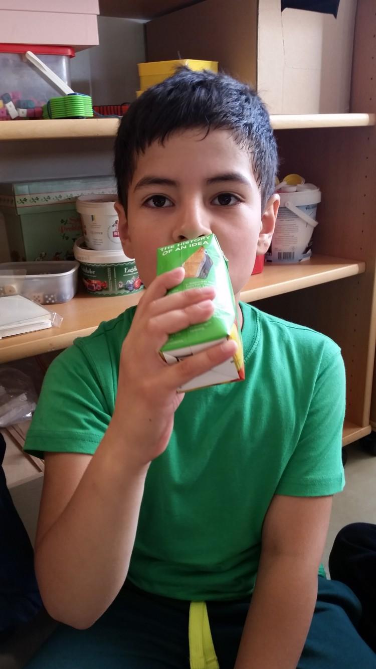 Barn dricker ur pappförpackning.