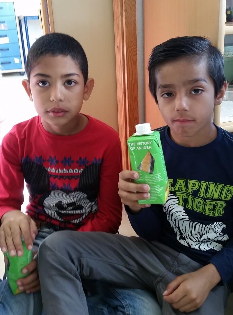 Två barn dricker ur pappföpackning.