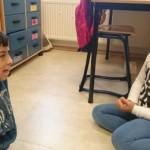 Barn sitter och pratar på golvet.
