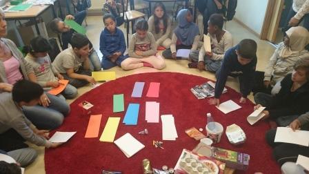 Elever sitter på golvet i cirkel.