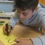 Pojke skriver på papper.