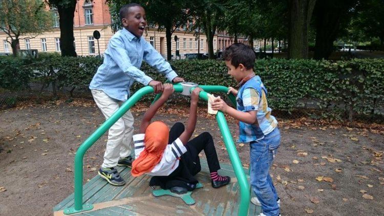 Tre barn leker på ställning.
