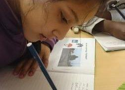 Elev skriver i häfte.