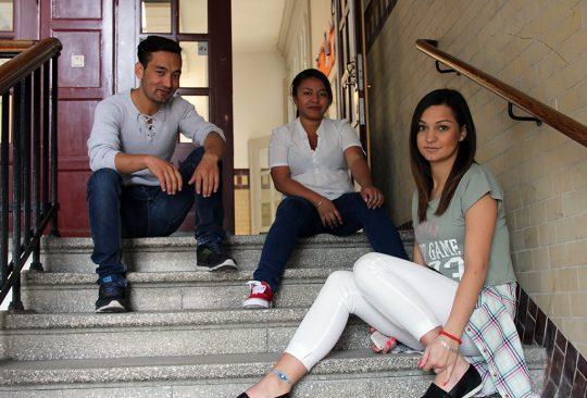 Tre elever sitter i stentrappa.