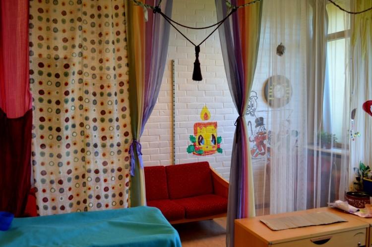 Röd soffa bakom gardiner.