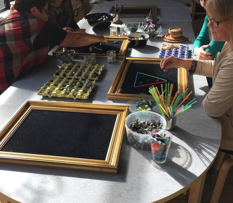 Pedagoger sitter vid bord med material.