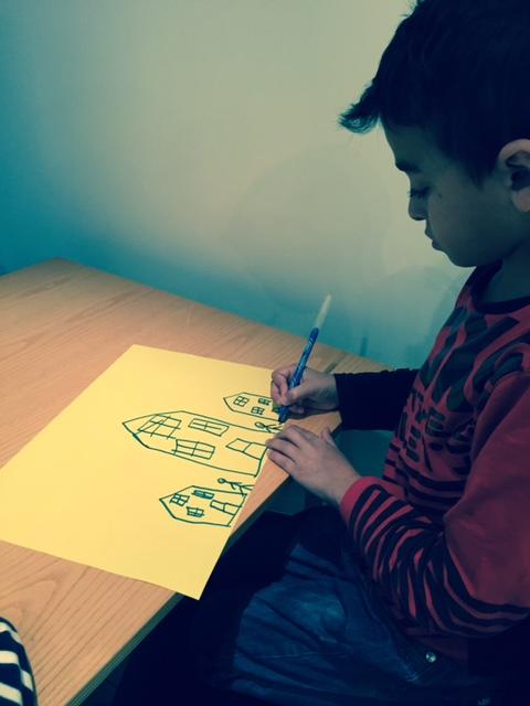 Pojke målar hus på papper.