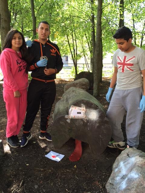Tre elever står vid sten.