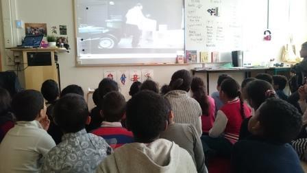 Barn sitter på golvet framför presentation.