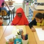 Barn skriver på sin text.