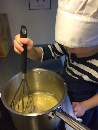Barn i kockmössa vispar i kastrull.