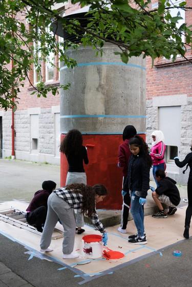 Elever målar rund cementpelare.
