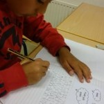 Elev jobbar med sin text i klassrummet.
