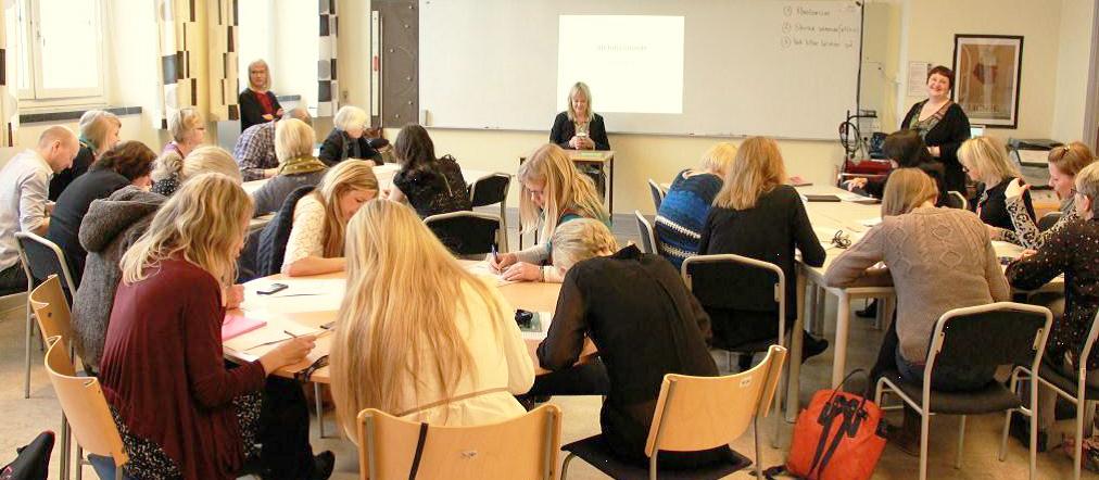 Pedagoger sitter vid olika runda bord och arbetar.