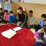 Pedagog sitter i cirkel på golv med barnen.