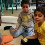 Tre elever sitter på golvet.