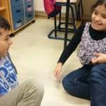 Två elever sitter på golvet.