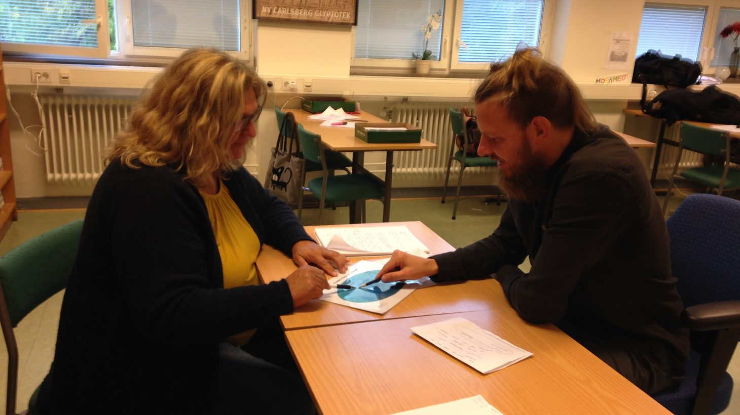 Kvinna och man sitter vid bord och pekar på papper.