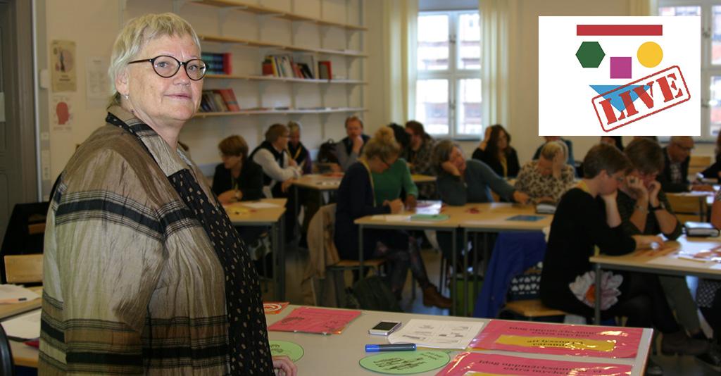Kvinna står längst fram i klassrum.