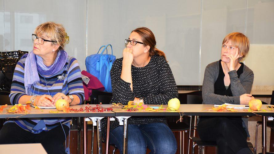 Tre kvinnor sitter vid bord.