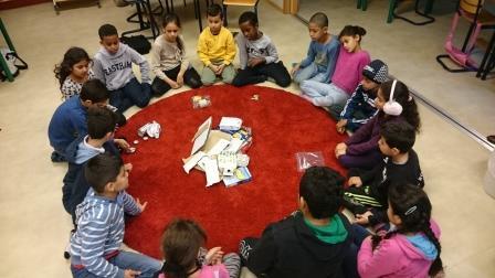 Barn sitter i cirkel på golvet.