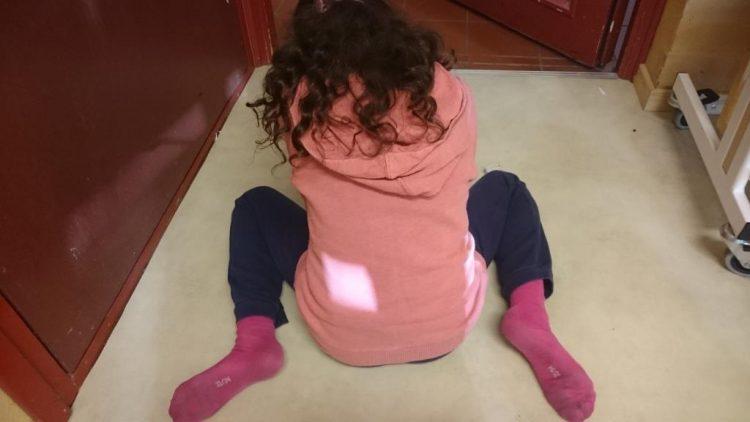 Barn sitter på golv.
