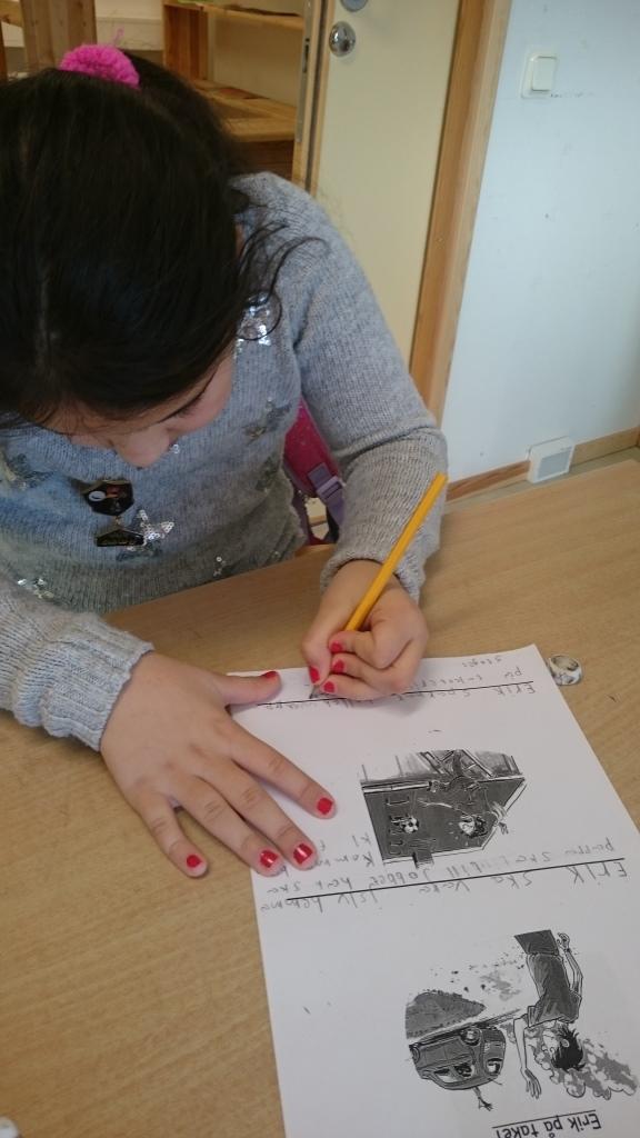 Barn skriver på papper.