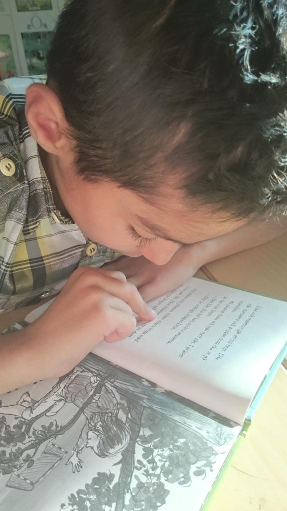 Barn läser bok och följer texten med fingret.