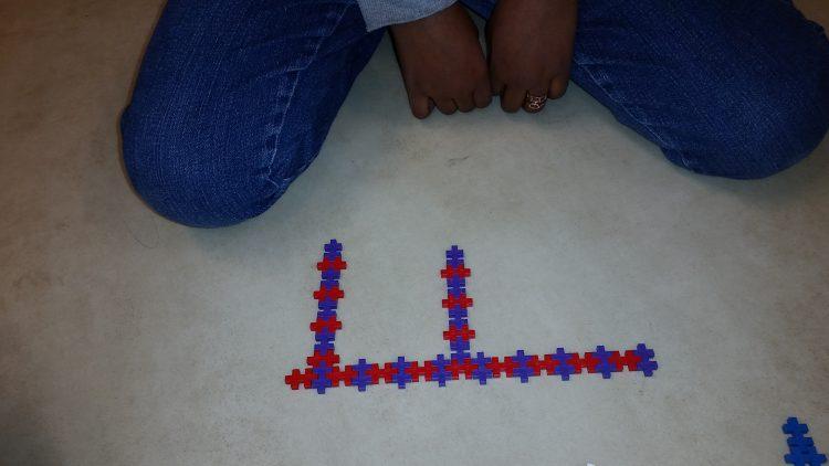 Barn visar upp plusplusbygge.