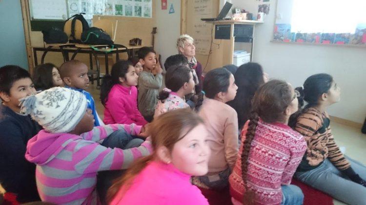Pedagog och barn sitter på golvet.