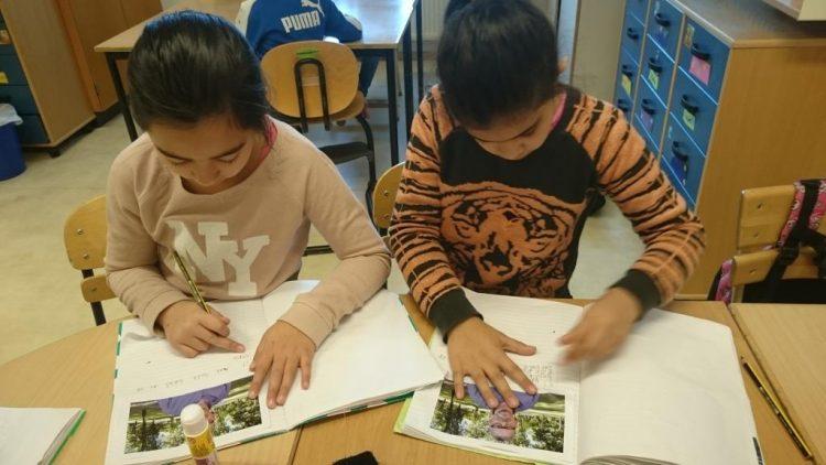 Barn skriver i texthäfte.