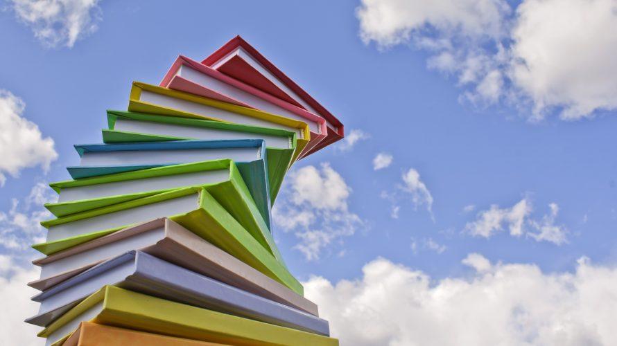 Böcker ligger i hög upp mot himlen.
