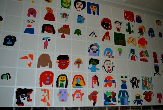 Porträtt målade av elever på vägg.