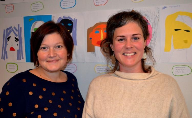Två kvinnor framför teckningar på vägg.