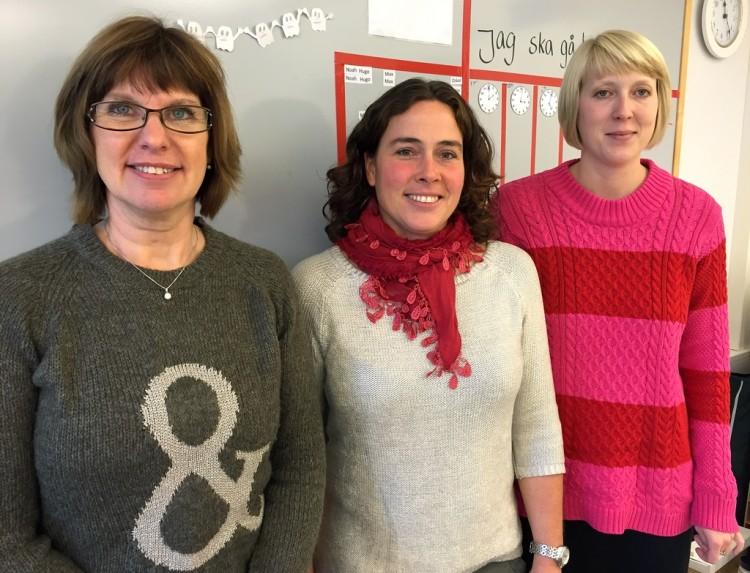 Tre kvinnor står vid anslagstavla.