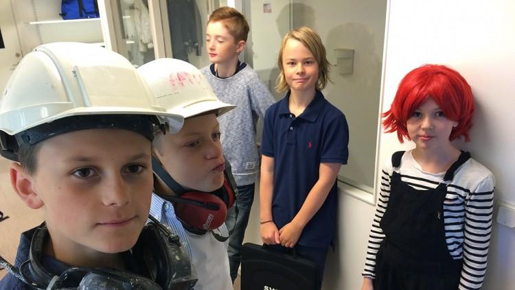 Fem elever varav två med hjälm.
