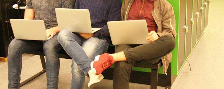 Tre elever sitter med laptops.