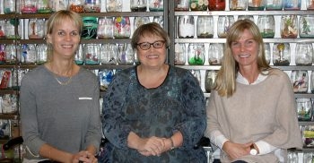 Tre kvinnor sitter på bänk framför massor av glasburkar fulla av material.