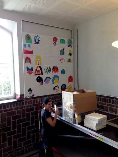 Elev står i trapphall med konstnärsmaterial.