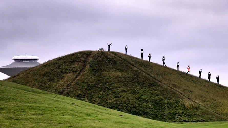 Barn står på grön kulle och håller upp saker ovanför huvudet.