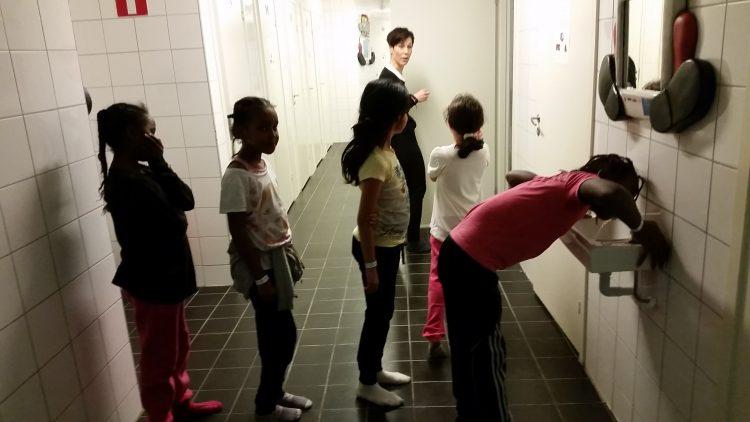 Barn i rad för att dricka ur fontän.