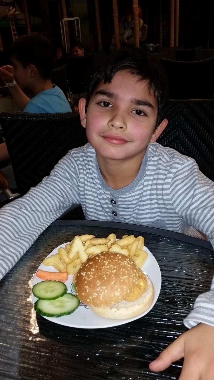 Barn äter hamburgare.