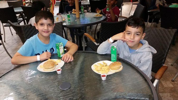 Två elever äter hamburgare.