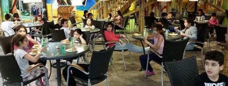 Barn sitter vid bord och fikar.
