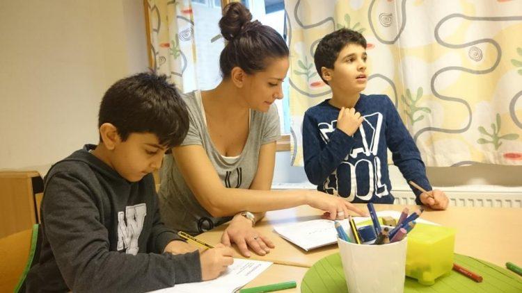 Kvinna hjälper två barn i klassrummet.