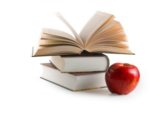 Rött äpple framför uppslagen bok.